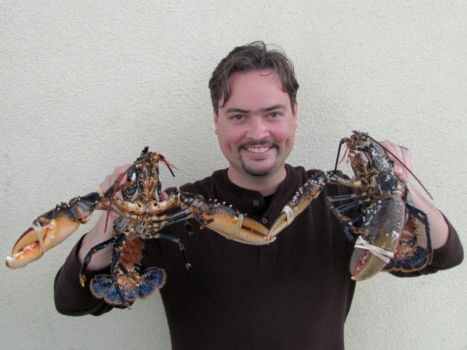 "Our visiting American friend Kane holding the two ""Homards bretons"": note how blue they are"