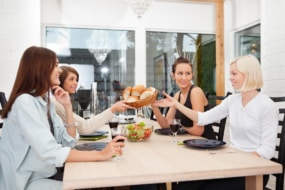 Friend passing basket filled with buns at dining table