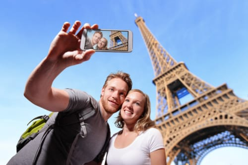 happy couple selfie by smart phone in Paris with eiffel tower, caucasian