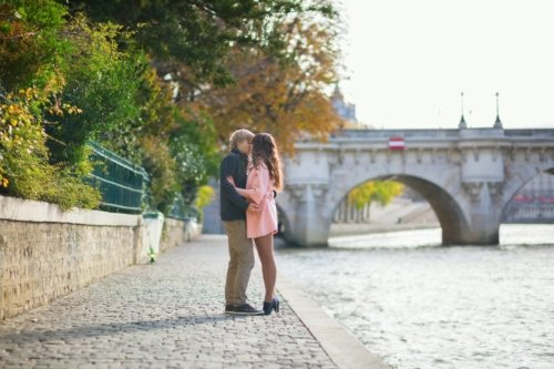 Romantic dating couple in Paris kissing near the Seine