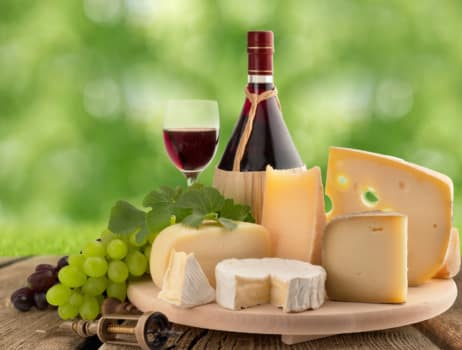 cheese board, grape and red wine on wooden table
