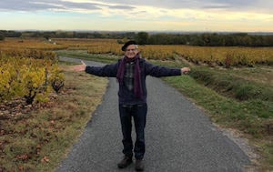 immersion student Stephen in front of gorgeous beaujolais landscape vines