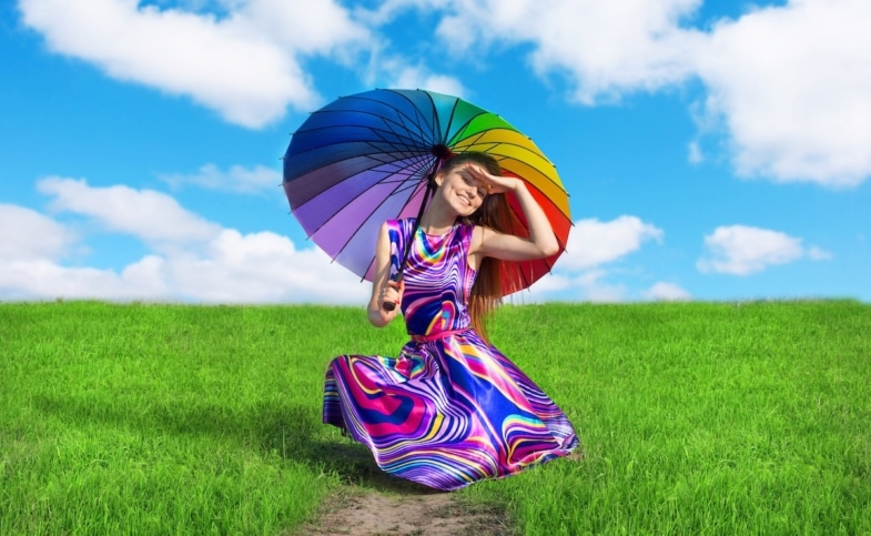 woman wearing a multi colored dress and rainbow umbrella