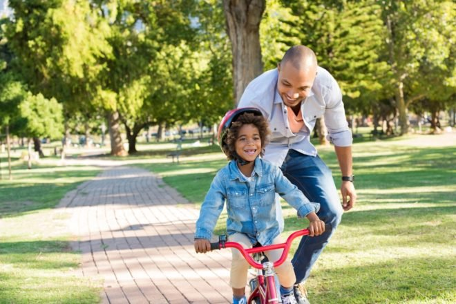 father supporting his kid riding a bike