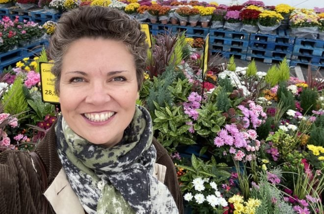 Camille in front of flowers for la Toussaint in France
